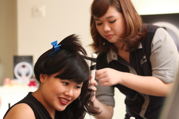 J salon's stylist helping to curl hair
